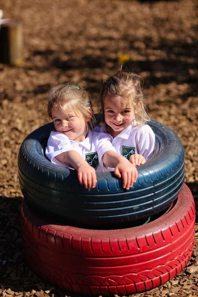 Two children sat in tires