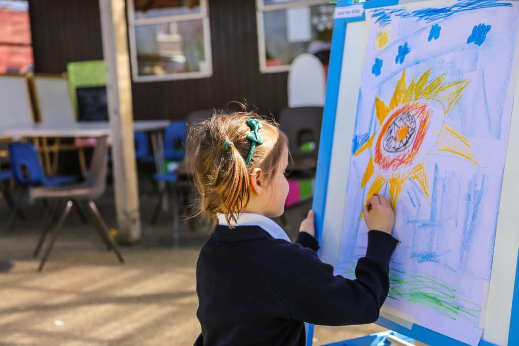 A girl outside school drawing a picture on a canvas