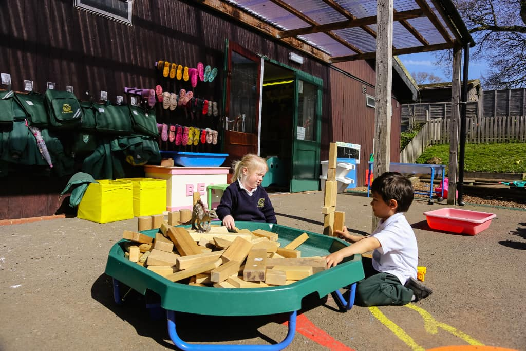 girls playing outside with blocks