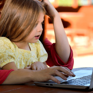 A child and her parent using a computer