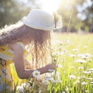 A girl with a hat in the field with daisies