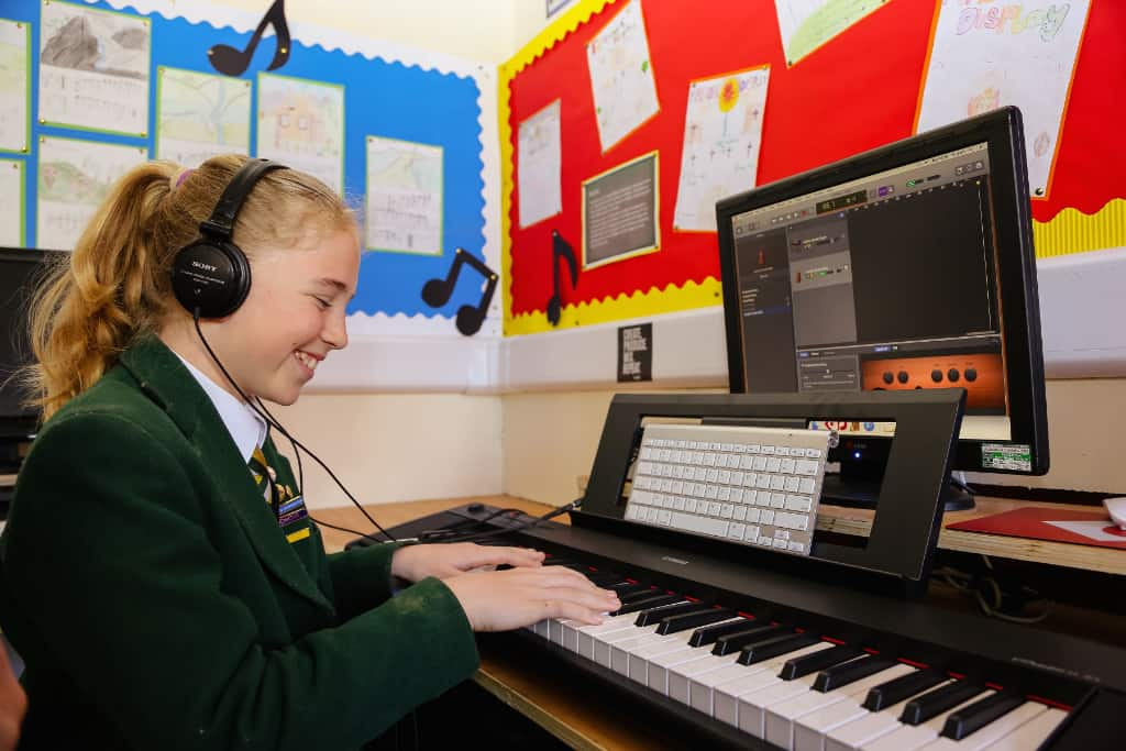 A girl playing the keyboard with headphones in