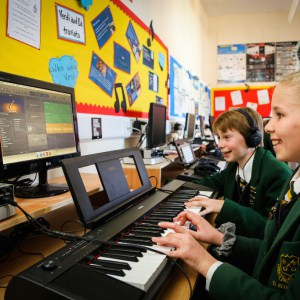 A picture of a girl and boy playing the keyboard