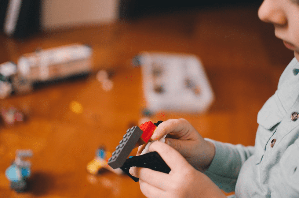 a picture of a boy playing with lego