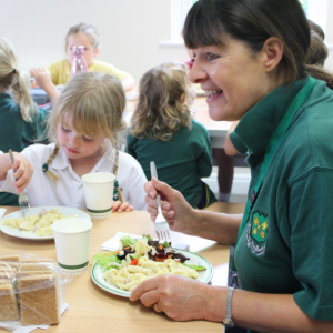 A teacher sitting with students having a meal