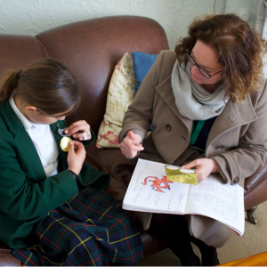 A girl receiving a sticker from the Head for her work going in the Book of Excellence