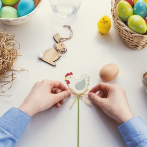 A child tying a straw bow at a table covered in Easter eggs