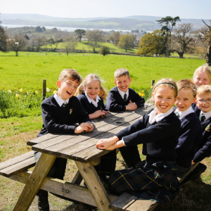 Children sitting around a picnic table talking