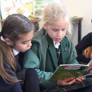 Three children sitting on the floor reading together