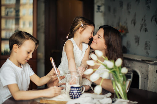 A mother sitting at a table with her two children