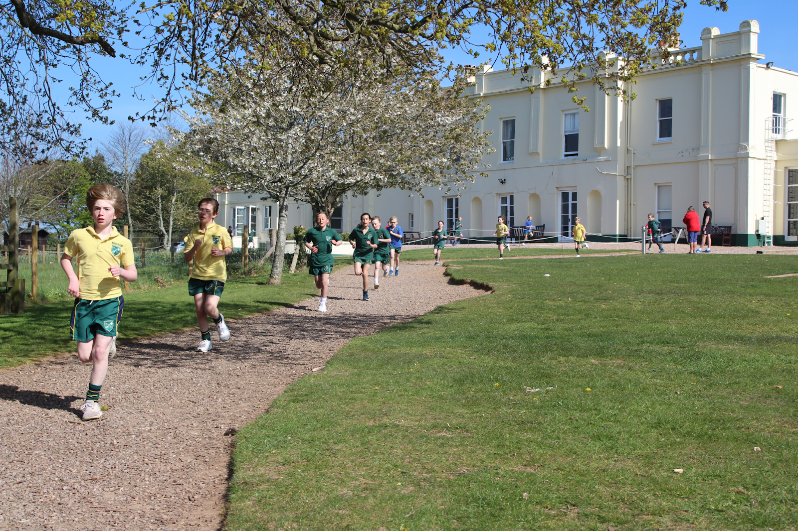 Pupils running down a school path