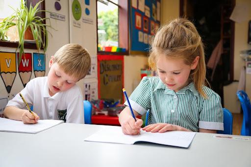 Children writing in exercise books
